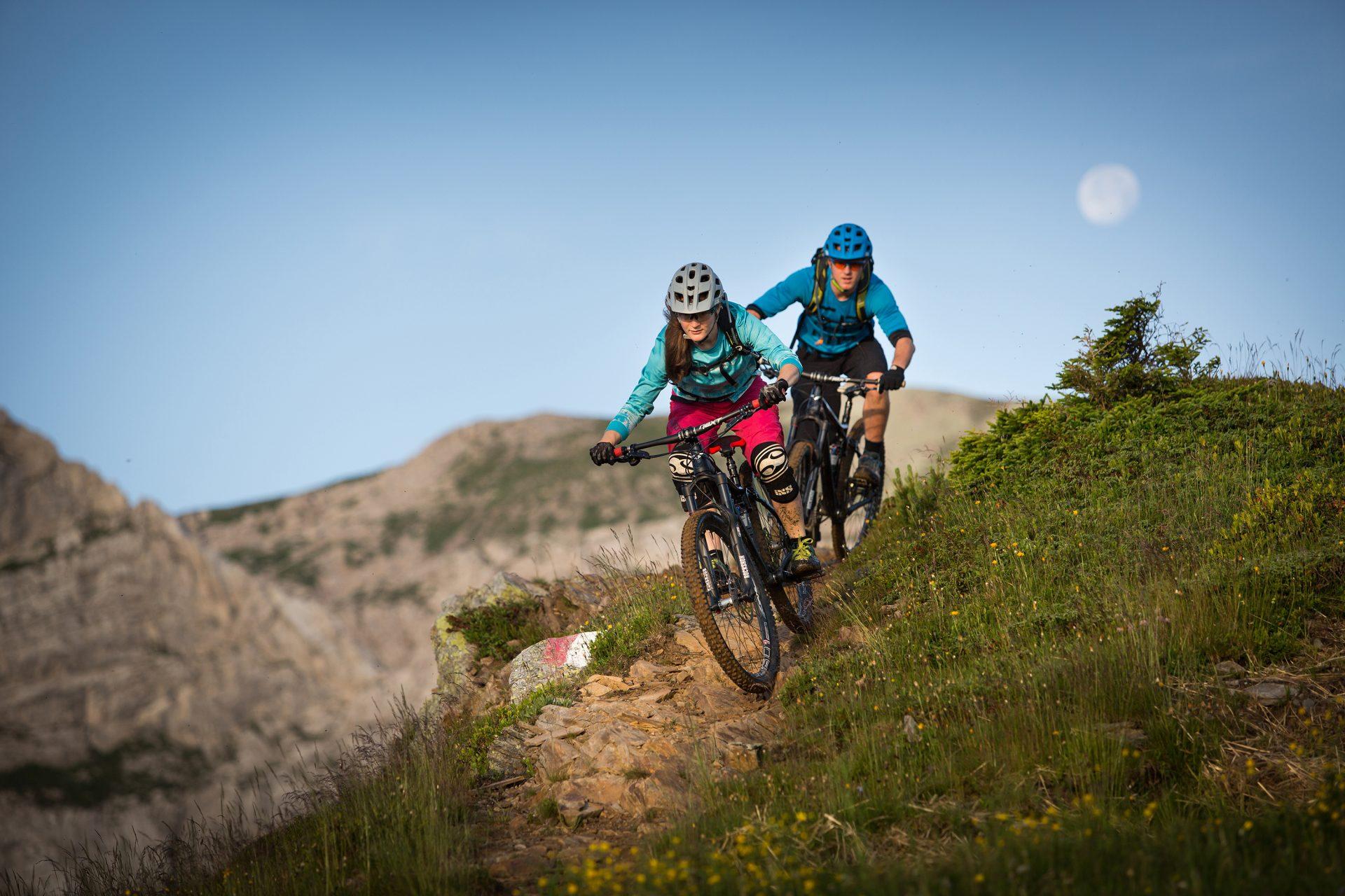 Zwei Mountainbiker auf einem Naturtrail am Nassfeld, im Hintergrund der Mond