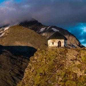 Die Kapelle auf der Arnoldhöhe oberhalb der Bergstation. Im Wolken im Hintergrund der Ankogel (3.252 m)